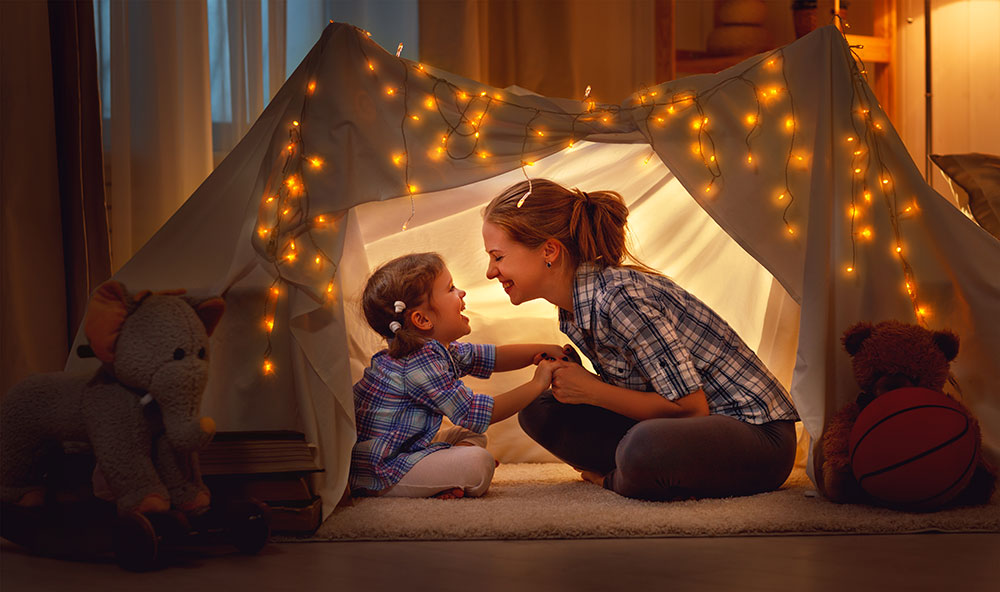 mom and daughter playing in a tent smiling